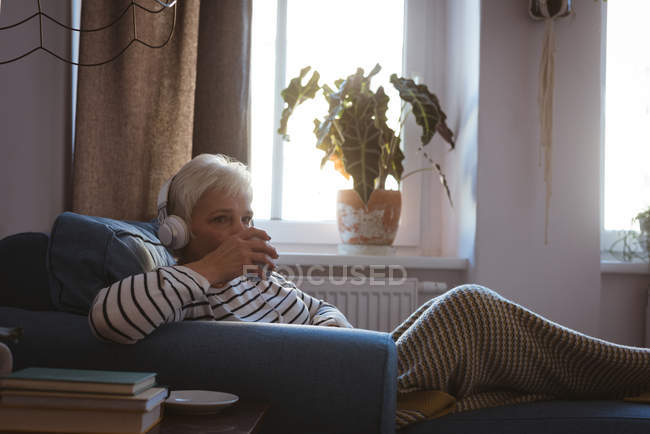 Senior woman relaxing on sofa listening to music with a cup of coffee in living room at home — Stock Photo