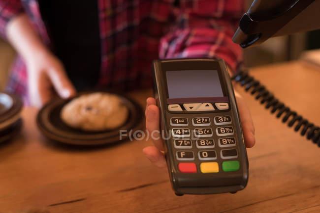 Section médiane de femme tenant paiement terminal au comptoir au café — Photo de stock