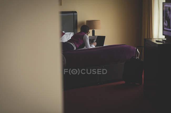 Hombre de negocios leyendo periódico en habitación de hotel - foto de stock
