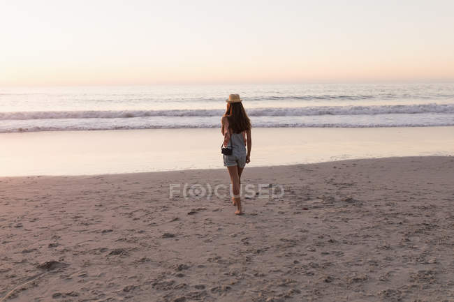 Woman in sunhat with vintage camera in beach at dusk. — Stock Photo