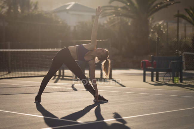 Young woman doing stretching exercise in the tennis court — Stock Photo