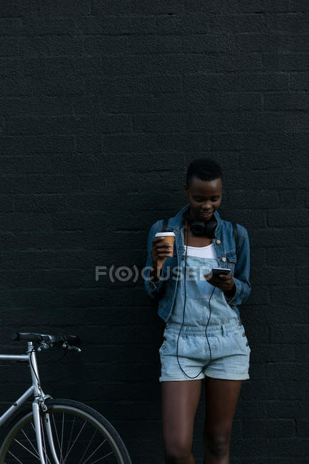 Woman having coffee while using mobile phone against wall — Stock Photo