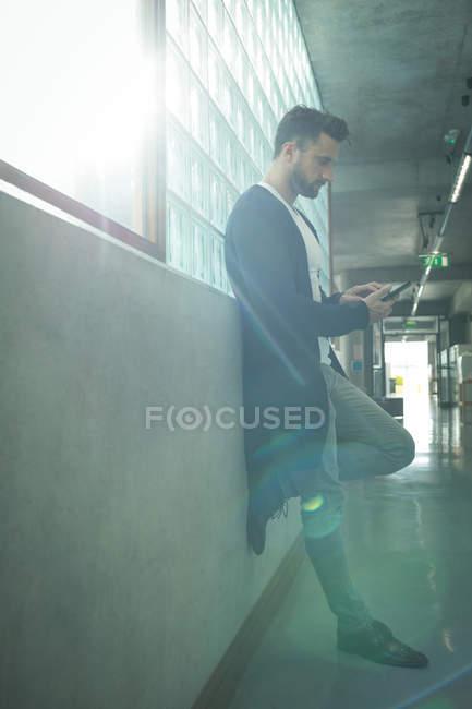 Vista lateral del ejecutivo masculino utilizando teléfono móvil en el pasillo de la oficina - foto de stock