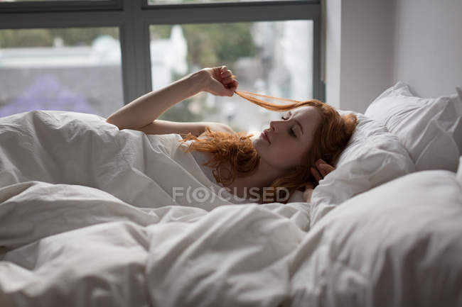 Thoughtful woman relaxing on bed in bedroom at home — Stock Photo