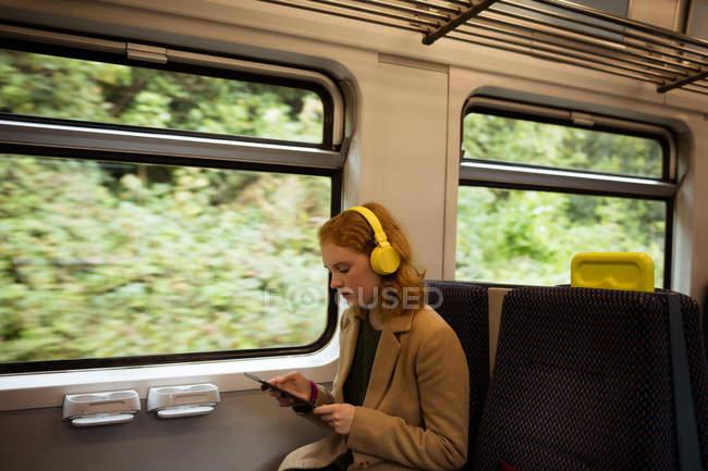 Jovem listando música enquanto usa tablet no trem — Fotografia de Stock