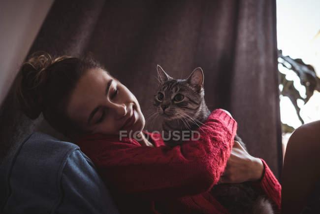 Крупный план улыбающейся женщины, обнимающей своего домашнего кота — стоковое фото