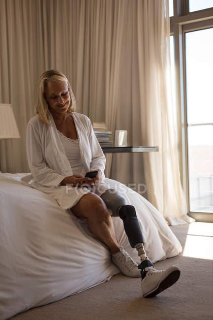 Reife Frau mit Beinprothese mit Handy im heimischen Schlafzimmer. — Stockfoto