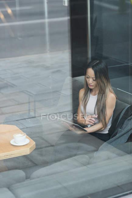 Asiatico businesswoman seduta da sola utilizzando il suo tablet in il lobby — Foto stock