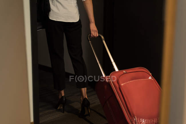 Businesswoman walking out of the hotel room with baggage — Stock Photo