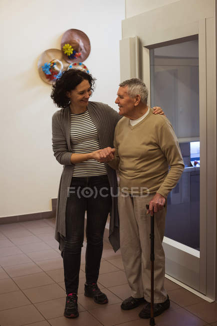 Caretaker talking to senior man at nursing home — Stock Photo