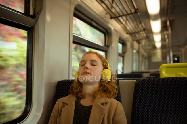 Jovem mulher relaxante enquanto listagem para música no trem — Fotografia de Stock