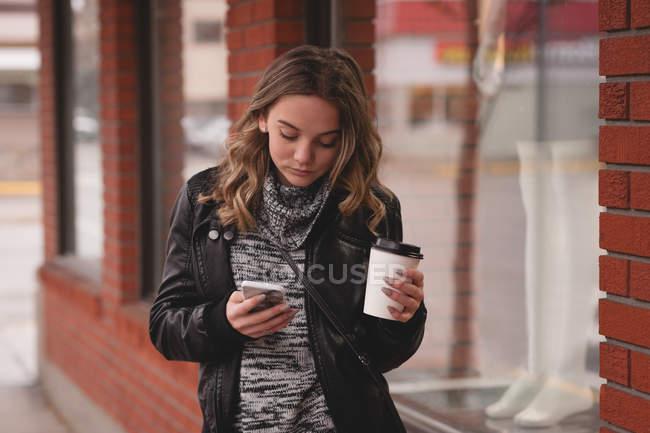 Linda garota usando celular enquanto tomar café fora do shopping — Fotografia de Stock