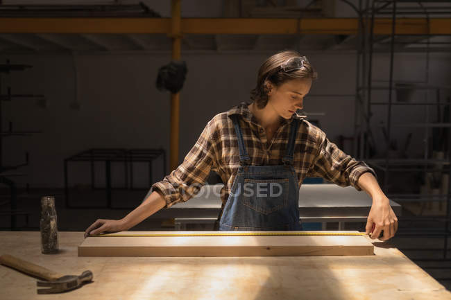 Young female artisan measuring wooden piece in workshop. — Stock Photo