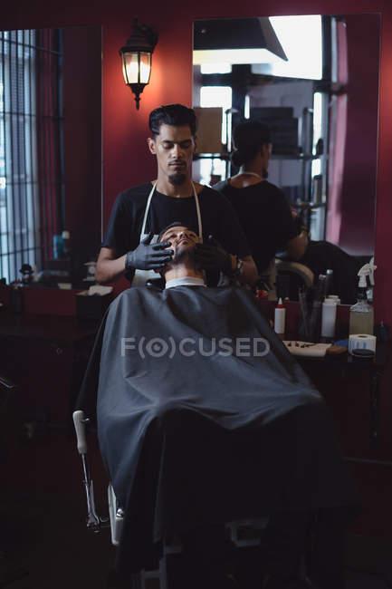 Мужской парикмахер нанесения крема на клиентов Борода в парикмахерской — стоковое фото