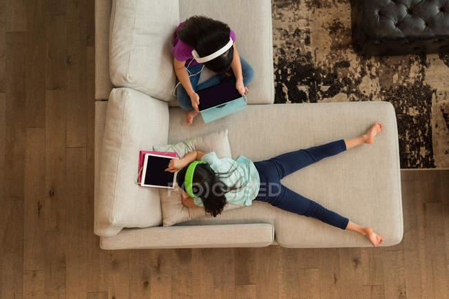 Vista aérea de hermanos con auriculares usando tableta digital en casa - foto de stock