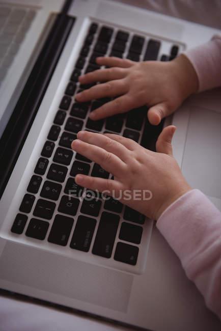 Primo piano della bambina che utilizza il computer portatile in camera da letto a casa — Foto stock