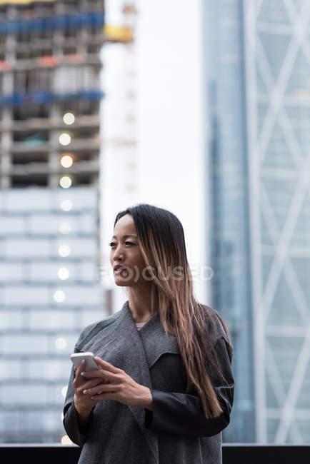 Бизнесвумен смотрит в сторону, используя свой мобильный телефон, стоящий напротив здания города — стоковое фото