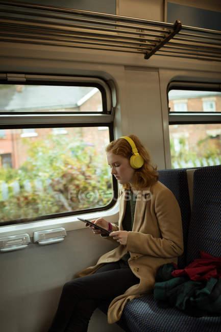 Jovem mulher, inclinar-se para a música enquanto estiver usando o tablet em trem — Fotografia de Stock