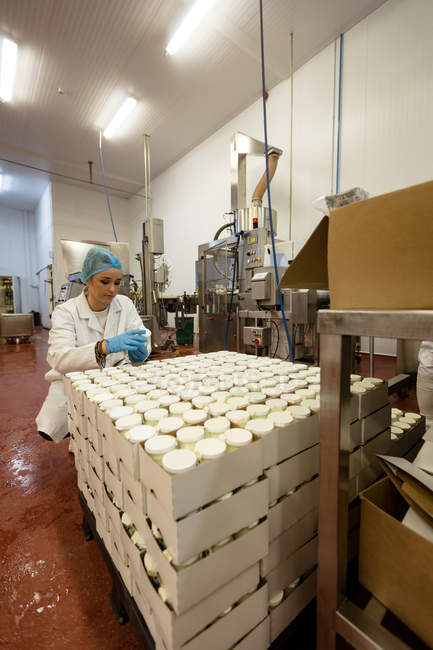 Travailleuse d'emballage de bouteilles dans l'usine d'aliments — Photo de stock