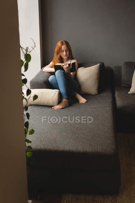 Donna che legge un libro a casa — Foto stock