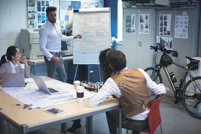 Exposé de la direction devant un collègue sur un tableau à feuilles mobiles au bureau — Photo de stock