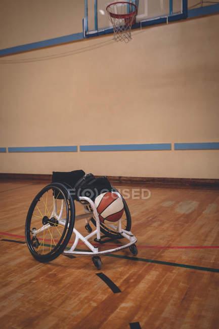Пустое инвалидное кресло и баскетбольный мяч на корте — стоковое фото