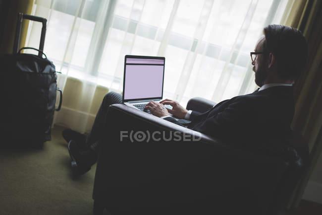 Geschäftsmann benutzt Laptop im Hotelzimmer — Stockfoto