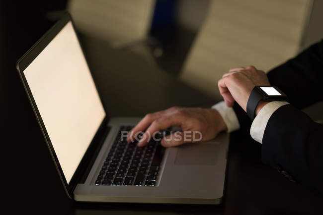 Businessman checking time while using laptop at desk in office — Stock Photo