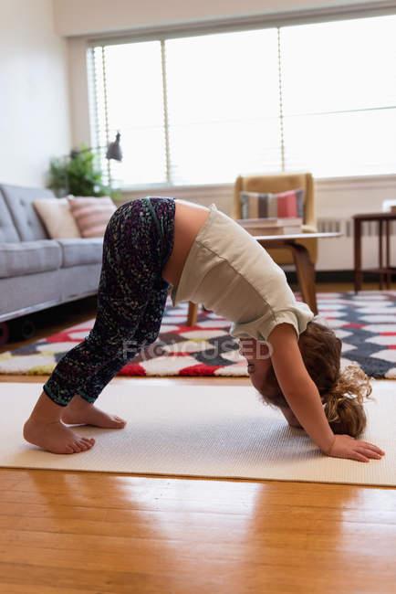 Nettes Mädchen macht Yoga im Wohnzimmer zu Hause — Stockfoto