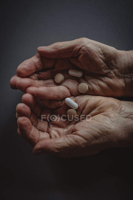 Close-up of senior womans cupped hands holding tablets — Stock Photo
