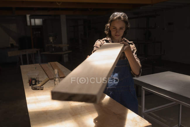 Young craftswoman examining wooden piece in workshop. — Stock Photo