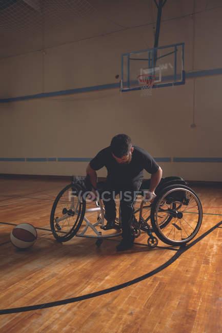 Молодой инвалид в инвалидной коляске на баскетбольной площадке — стоковое фото