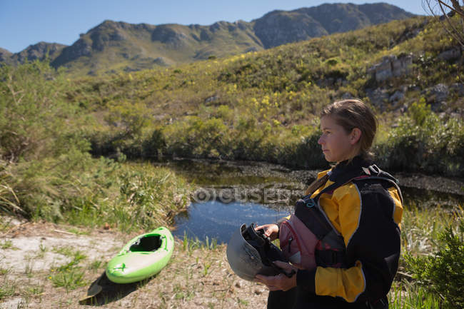 Femme debout à l'extérieur avec bateau kayak sur berge en montagnes — Photo de stock