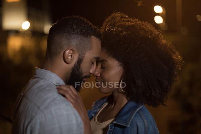 Pareja romántica abrazar mutuamente en el camino en la noche - foto de stock