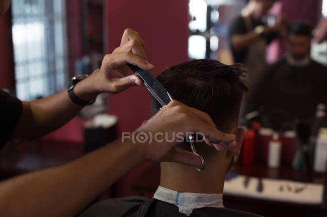 Мужчина стрижёт волосы триммером в парикмахерской — стоковое фото