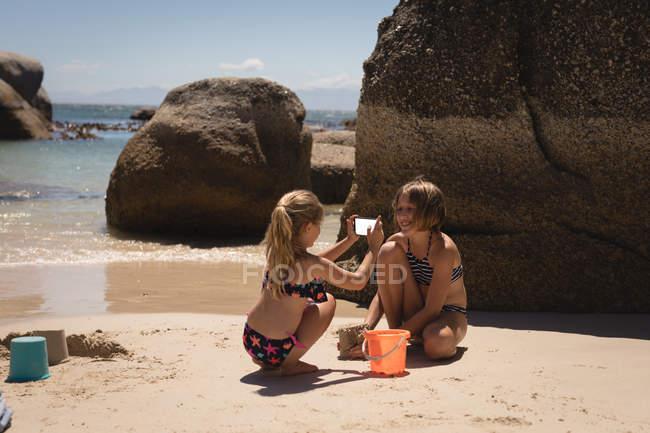 Chica tomando fotos de su hermano con teléfono móvil en la playa - foto de stock