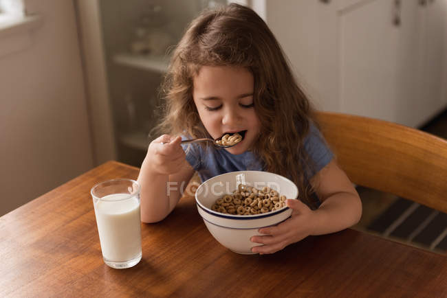 Girl having breakfast cereal and milk on table at home — Stock Photo