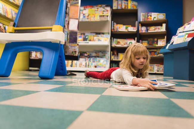 Mädchen lesen ein Buch im Buchladen — Stockfoto