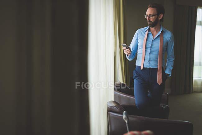 Uomo d'affari che utilizza il telefono cellulare in camera d'albergo — Foto stock