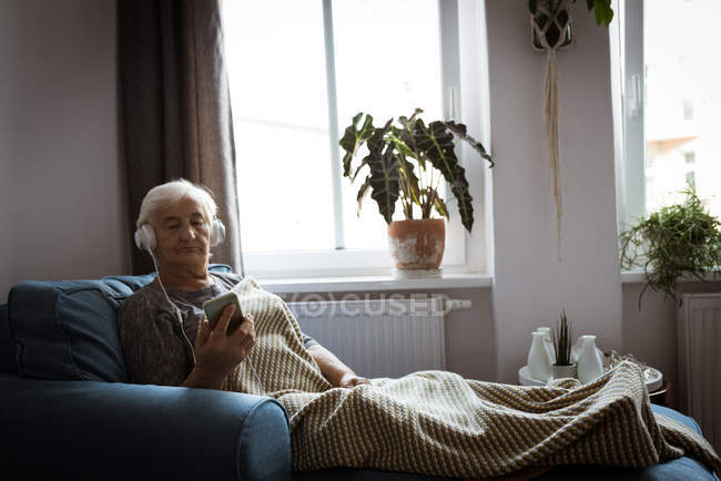 Senior woman listening to music on headphones while using mobile phone in living room — Stock Photo