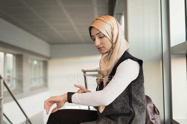 Young woman in hijab using smartwatch — Stock Photo