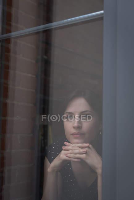 Жіночий виконавчий дивлячись через вікно в офісі — стокове фото