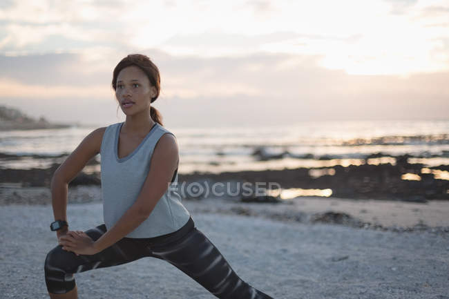 Женщина, занимающаяся на пляже на закате — стоковое фото