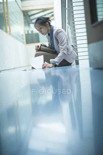 Жіночий виконавчий читання документа у сучасні офісні — стокове фото