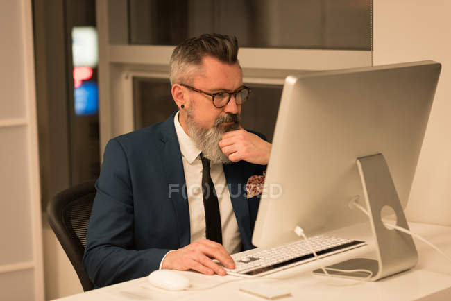 Business executives working on computer in office — Stock Photo
