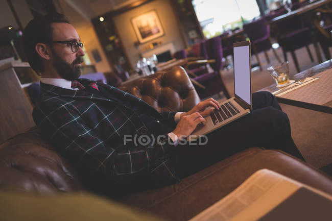 Homme d'affaires utilisant un ordinateur portable dans le bar — Photo de stock