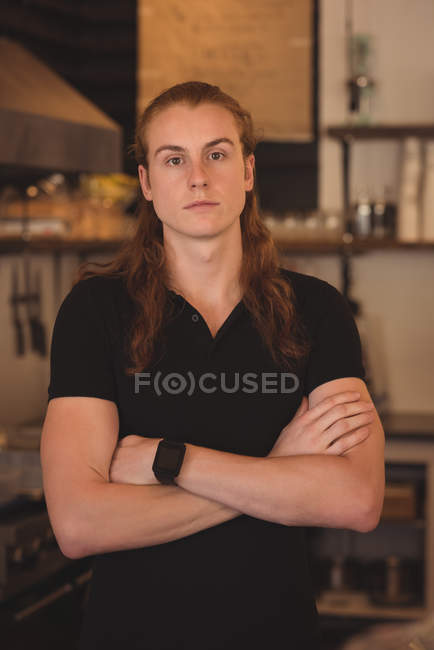 Portrait of confidence waiter standing with arms crossed in cafe — Stock Photo