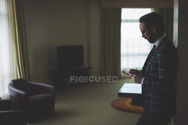 Geschäftsmann benutzt Handy im Hotelzimmer — Stockfoto