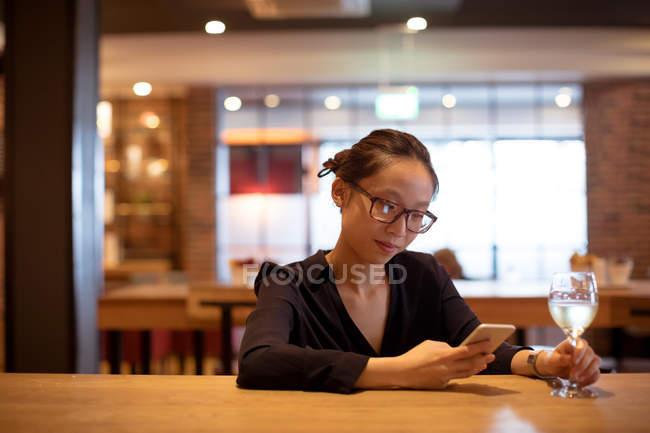 Femme utilisant un téléphone portable tout en ayant du vin à l'hôtel — Photo de stock
