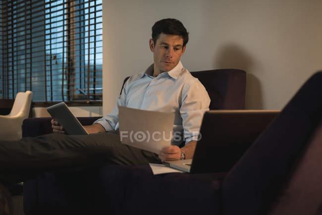 Uomo d'affari verifica documenti durante l'utilizzo di tablet digitale in camera da letto — Foto stock